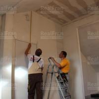мастер производит замер натяжного потолка
